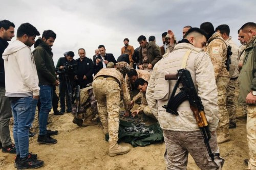 Iraqi security forces gather to inspect the site after Iran's Islamic Revolutionary Guard Corps (IRGC) targeted an airbase in Iraq, a facility jointly operated by US and Iraqi forces on 8 January 2020 [Azad Muhammed/Anadolu Agency]