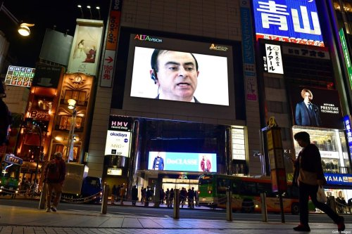 A pedestrian walks past a screen showing a news programme featuring Nissan chairman Carlos Ghosn in Tokyo on November 22, 2018 [KAZUHIRO NOGI/AFP via Getty Images]