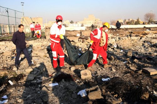Rescue teams recover a body after a Ukrainian plane carrying 176 passengers crashed near Imam Khomeini airport in the Iranian capital Tehran early in the morning on January 8, 2020, killing everyone on board [AFP via Getty Images]