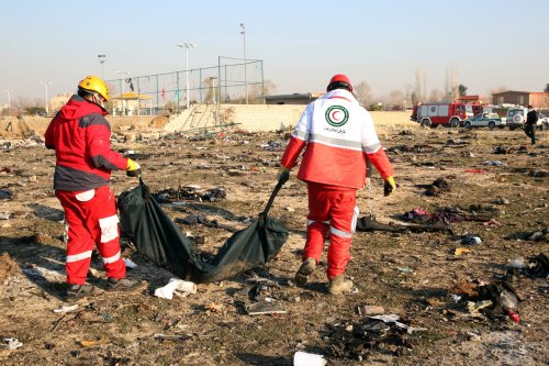 Officials inspect pieces of a Boeing 737 plane belonging to Ukrainian International Airlines after it crashed in Iran on 10 January 2020 [AFP/Getty Images]