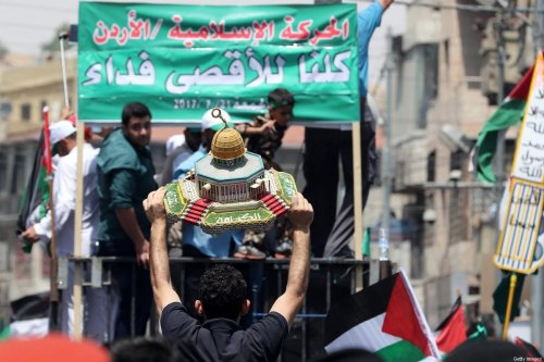Jordanians carry a model of the Dome of the Rock mosque during a demonstration, called for by the Islamic Action Front, in Amman following friday prayers on July 21, 2017 [KHALIL MAZRAAWI/AFP via Getty Images]
