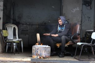 A Palestinian man tries to keep warm as heavy rain hits Gaza on 9 January 2020 [Mohammed Asad/Middle East Monitor]