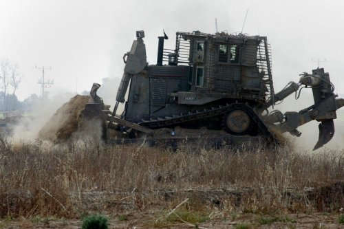 An Israeli bulldozer works along a barbed wire fence between Gaza and Israel on 10 June 2015 [Abed Rahim Khatib/Apaimages]