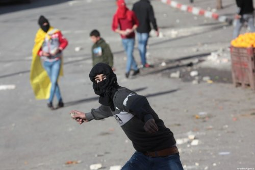 A protester prepares to throw a rock in response to Israeli forces' intervention in a protest against U.S. President Donald Trump's Middle East plan, in Hebron, West Bank on January 30, 2020 [Mamoun Wazwaz/Anadolu Agency]