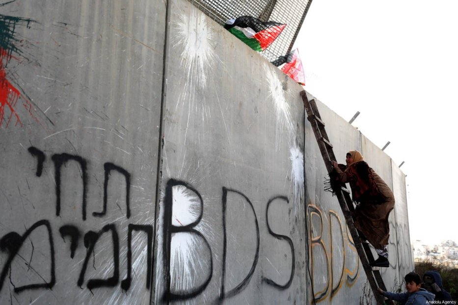 Palestinians try to cross separation wall during a protest against US President Donald Trump's Middle East plan in Ramallah, West Bank on 31 January 2020. [Issam Rimawi - Anadolu Agency]