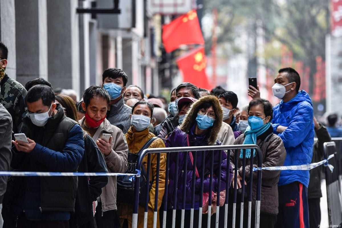 People are seen queuing for a shop to buy face masks, in response to the coronavirus outbreak, on February 1,2020 in Guangzhou, China [Stringer / Anadolu Agency]