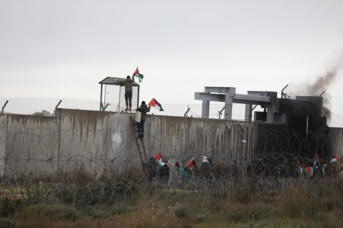 A Palestinian demonstrator tries to put a flag on an iron cabin as they gather at the separation wall during a protest against US President Donald Trump's Middle East plan near at Bil'in town in Ramallah, West Bank on 7 February 2020. [Issam Rimawi - Anadolu Agency ]