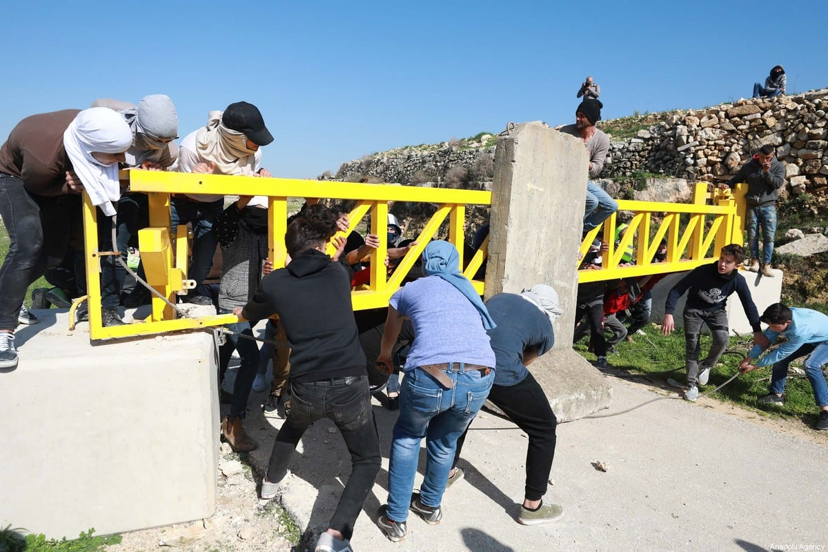 Palestinian youths from the village of Deir Nizam, northwest of Ramallah in the occupied West Bank, try to remove cement blocks from the village entrance on 15 February, 2020 [Issam Rimawi/Anadolu Agency]
