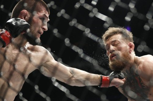 Khabib Nurmagomedov, (L), punches Conor McGregor during a lightweight title mixed martial arts bout at UFC 229 in Las Vegas, US [AP Photo]