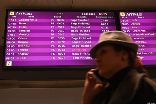 A woman uses a smartphone as she walks past an arrivals board displaying the Ukraine International Airlines Flight PS752 from Tehran marked as cancelled at the Boryspil airport outside Kiev on 8 January 2020. [SERGEI SUPINSKY/AFP via Getty Images]