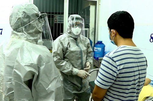 Medical personnel wearing protectice suits interact with two patients (R on bed and standing) tested positive to the coronavirus in an isolation room at Cho Ray hospital in Ho Chi Minh City on January 23, 2020 [STR/Vietnam News Agency/AFP via Getty Images]