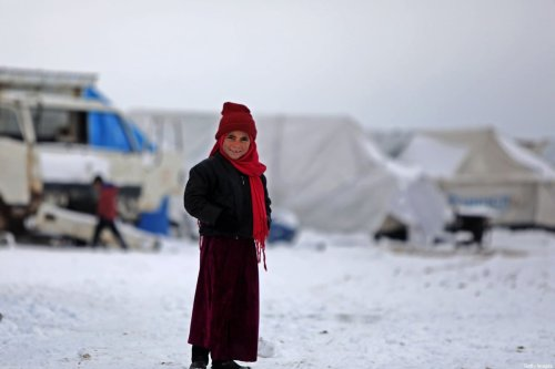 A child who fled pro-regime forces attacks in northeastern Syria, is pictured in front of tents at camp for displaced people in the northern Syrian town of Tal Abyad by the border with Turkey, on February 13, 2020. [BAKR ALKASEM/AFP via Getty Images]