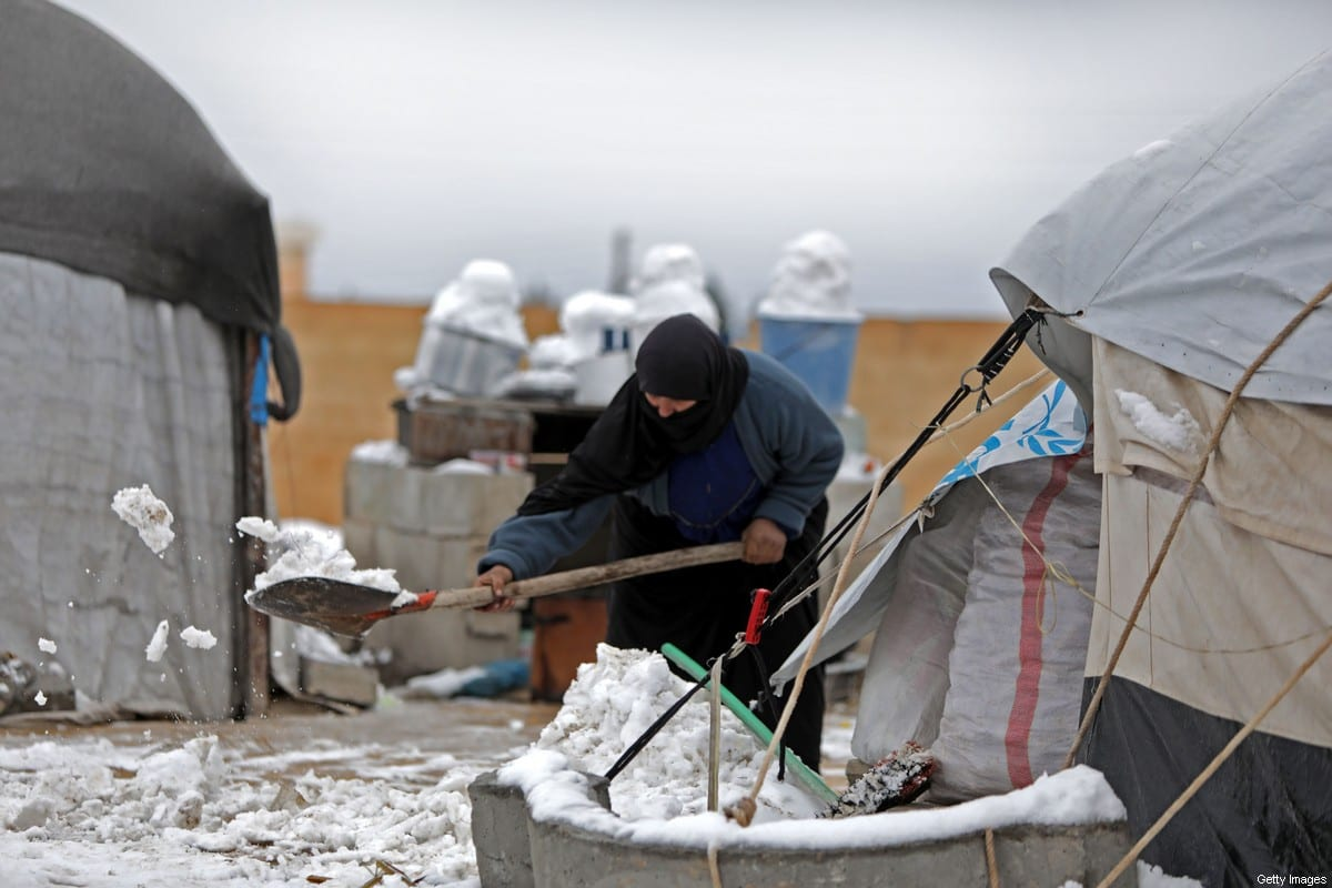 A woman who fled regime forces' attacks in northeastern Syria, clears the snow in front of a tent at camp for displaced people in the northern Syrian town of Tal Abyad by the border with Turkey, on February 13, 2020 [BAKR ALKASEM/AFP via Getty Images]