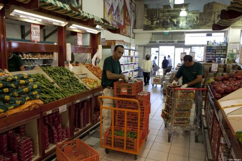 Palestinian workers put on display vegetables at a large Israeli settler-owned supermarket located at the Gush Etzion junction in the Palestinian West Bank on July 4, 2010 [MENAHEM KAHANA/AFP via Getty Images]