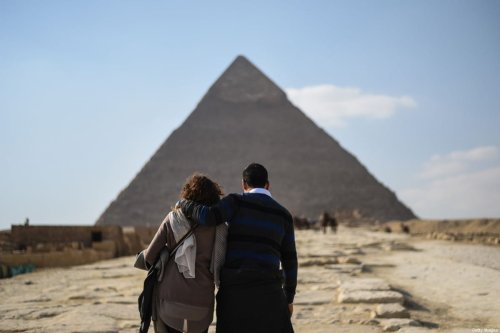 A couple look at one of the Giza pyramids in the southern Cairo Giza district on January 20, 2016. Since Egypt's then army chief and now President Abdel Fattah al-Sisi ousted Islamist leader Mohamed Morsi in 2013, a deadly insurgency led by the Islamic State jihadist group has kept away millions of tourists. / AFP / MOHAMED EL-SHAHED / TO GO WITH AFP STORY BY JAY DESHMUKH (Photo credit should read MOHAMED EL-SHAHED/AFP via Getty Images)