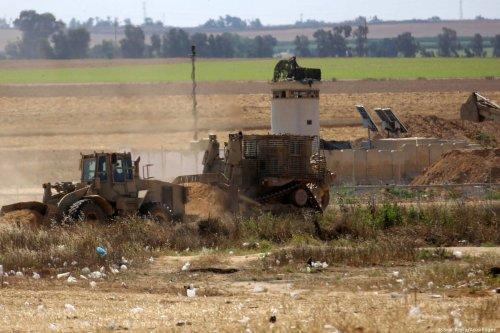 Israeli bulldozers can be seen near the Gaza-Israel fence on 9 May 2018 [Ashraf Amra/ApaImages]