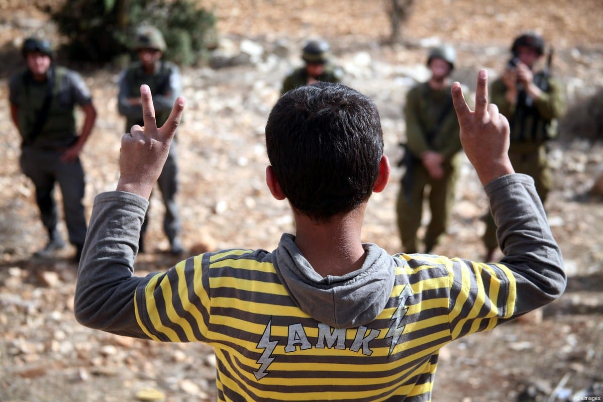 A Palestinian child waves with victory sign in front Israeli soldiers during a demonstration held by Palestinians, Israeli and foreign protesters near the Karmi Tsur Jewish settlement not far from the Palestinian village of Beit Omar in the Israeli-occupied West Bank on November 06, 2010.. [Najeh Hashlamoun/ApaImages]