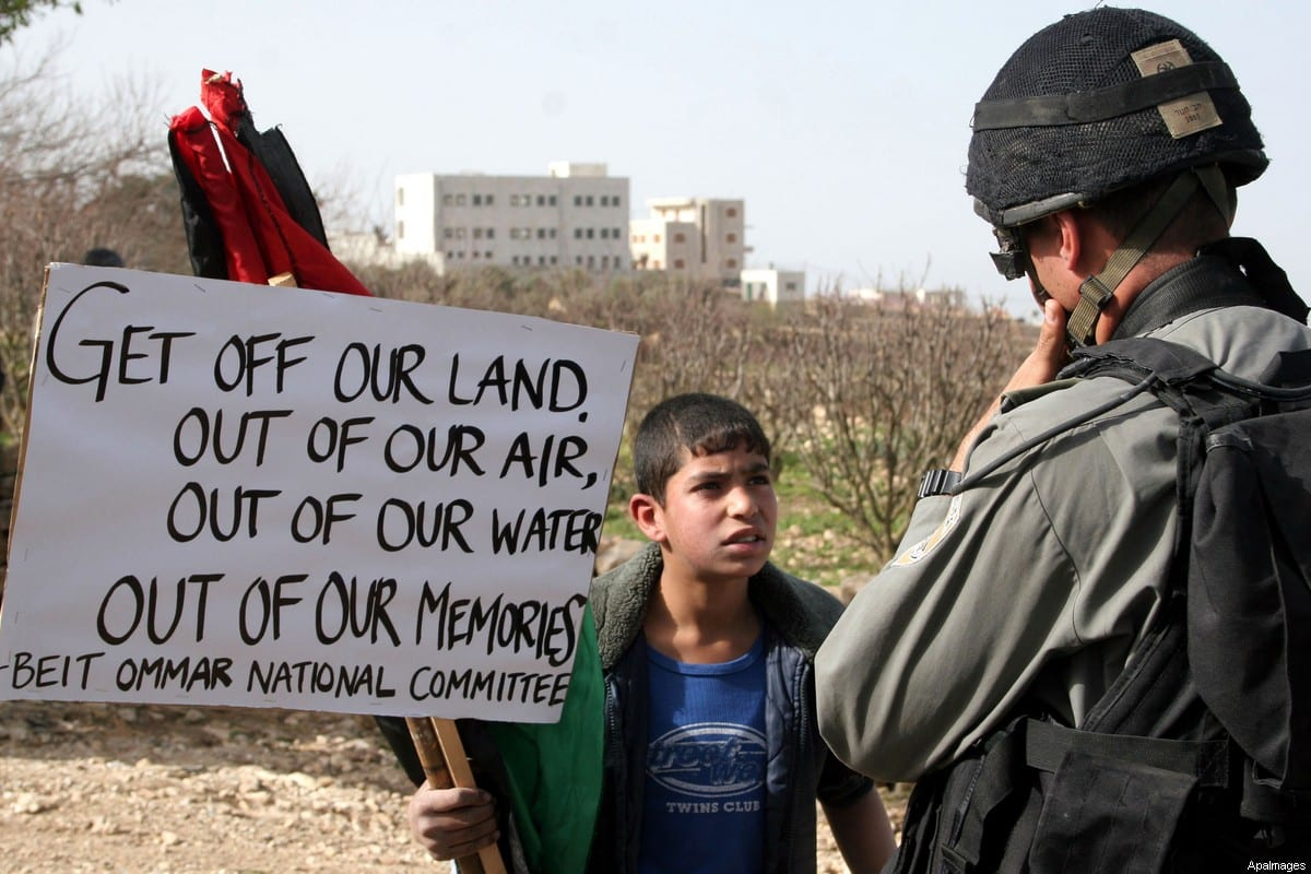 A Palestinian boy hold a banner in front of Israeli soldier in the West Bank village of Safa near Hebron Feb 13,2010. Photo by Najeh Hashlamoun/ApaImages