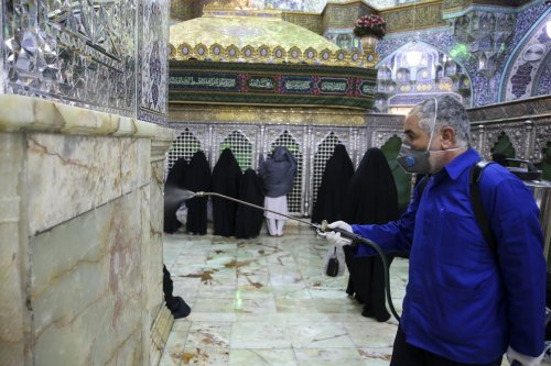 Officials carry out disinfection works as restrictions have been placed on religious ceremonies to prevent spreading coronavirus in Qom, Iran on 25 February 2020 [Stringer/Anadolu Agency]