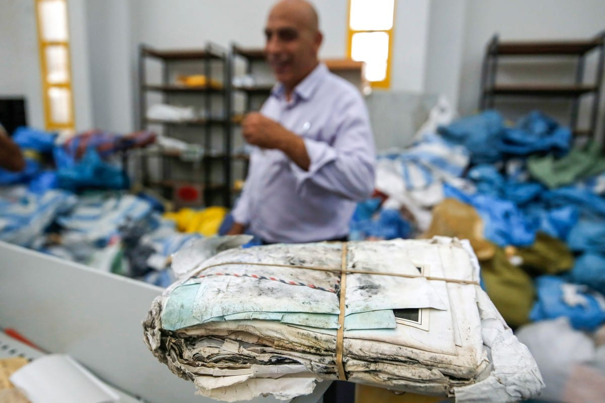 A picture taken on August 14, 2018 shows stacks of undelivered mail dating as far back as 2010 which has been withheld by Israel [ABBAS MOMANI/AFP via Getty Images]