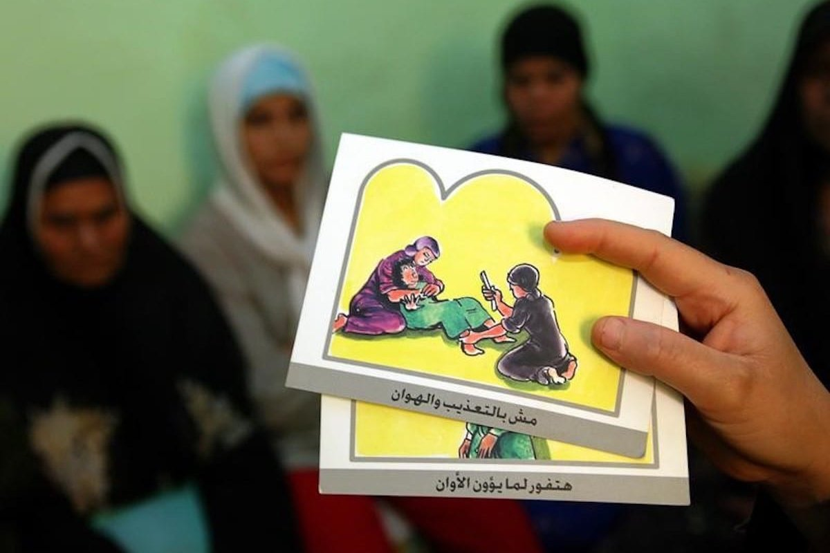 A counsellor holds up cards used to educate women about female genital mutilation (FGM) in Minia June 13, 2006. [Reuters]