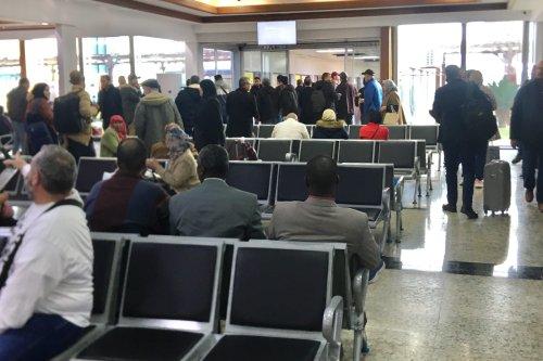 People wait at Mitiga International Airport after aviation was suspended following militias loyal to Libyan warlord Khalifa Haftar targeted Mitiga International Airport in the capital Tripoli, Libya on February 27, 2020. [Hazem Turkia - Anadolu Agency]