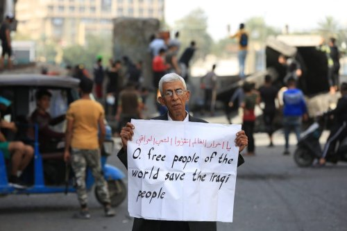 An old man holds a banner at Al-Khulani Square for an anti-government protest in Baghdad, Iraq on 6 March 2020. [Murtadha Al-Sudani - Anadolu Agency]