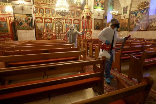 Municipality workers with protective suits disinfect churches as a precaution against the spread of the COVID-19 coronavirus in Ramallah, West Bank on 7 March 2020. [Issam Rimawi - Anadolu Agency]