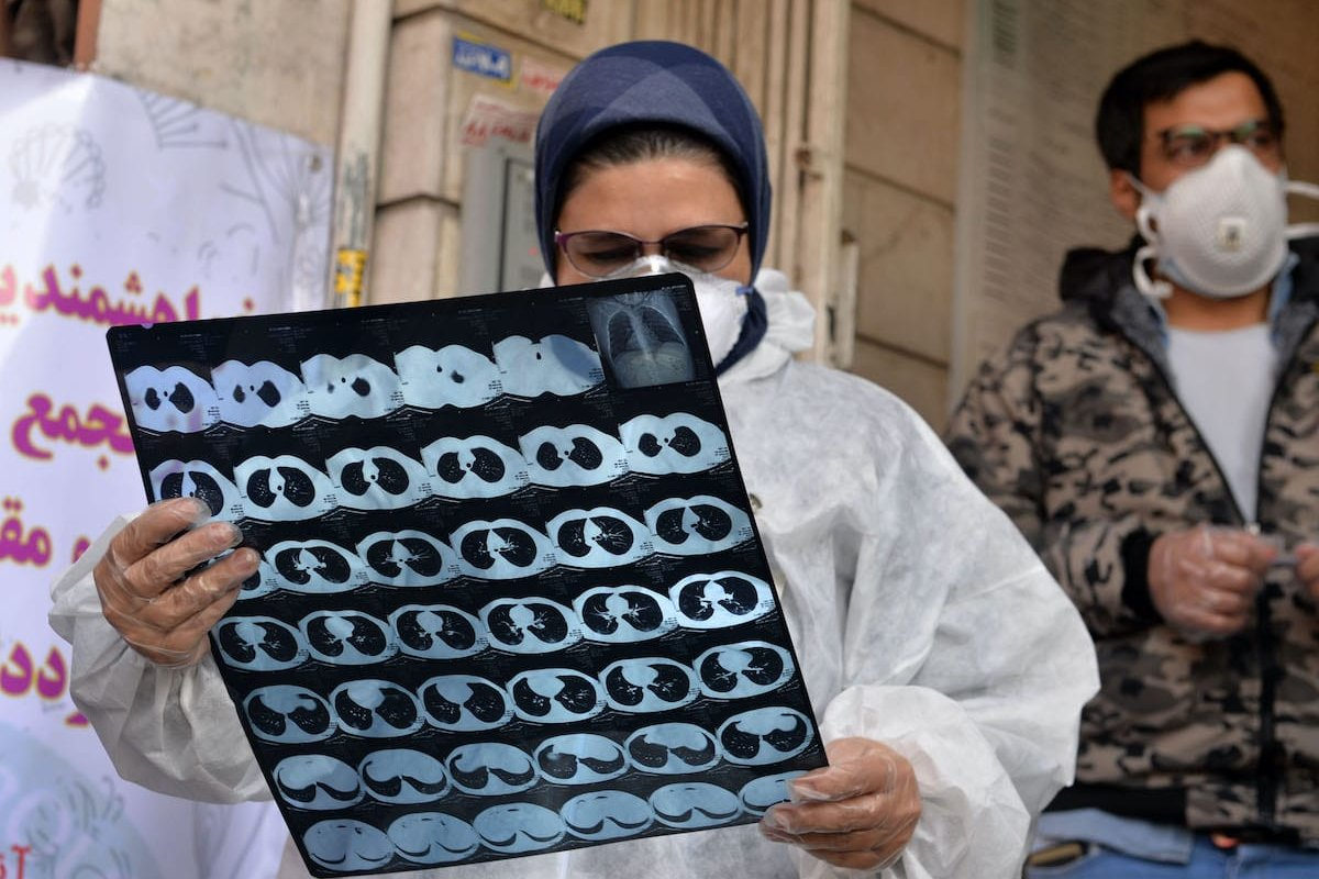 A medical staff examines a sample from a patient at Keyvan Virology Laboratory to confirm the coronavirus cases in Tehran, Iran on 10 March 2020. [Fatemeh Bahrami - Anadolu Agency]