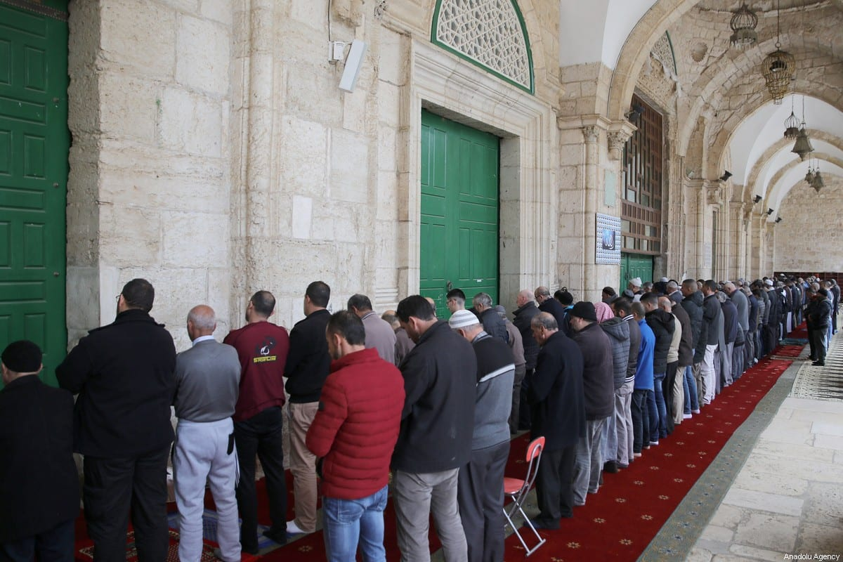 Muslims perform prayer outside the Al-Aqsa Mosque after the Islamic Waqf Department announced to close the enclosed prayer places as a precautionary measure to prevent the spread of the coronavirus (COVID-19) outbreak in Jerusalem on 15 March, 2020 [Mostafa Alkharouf/Anadolu Agency]