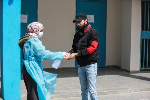 A healthcare worker gives hand sanitizer to a man at a school-turned-clinic by the UNRWA for patients with respiratory system disorders as a precaution against the coronavirus (COVID-19) in Gaza City, Gaza on March 18, 2020 [Ali Jadallah / Anadolu Agency]
