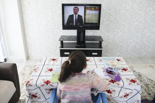 A student watches Turkish National Education Minister Ziya Selcuk from the TV at her house as the Minister giving a first lecture of distance education program, on 23 March 2020 in Sanliurfa, Turkey. [Mehmet Fatih Aslan - Anadolu Agency]