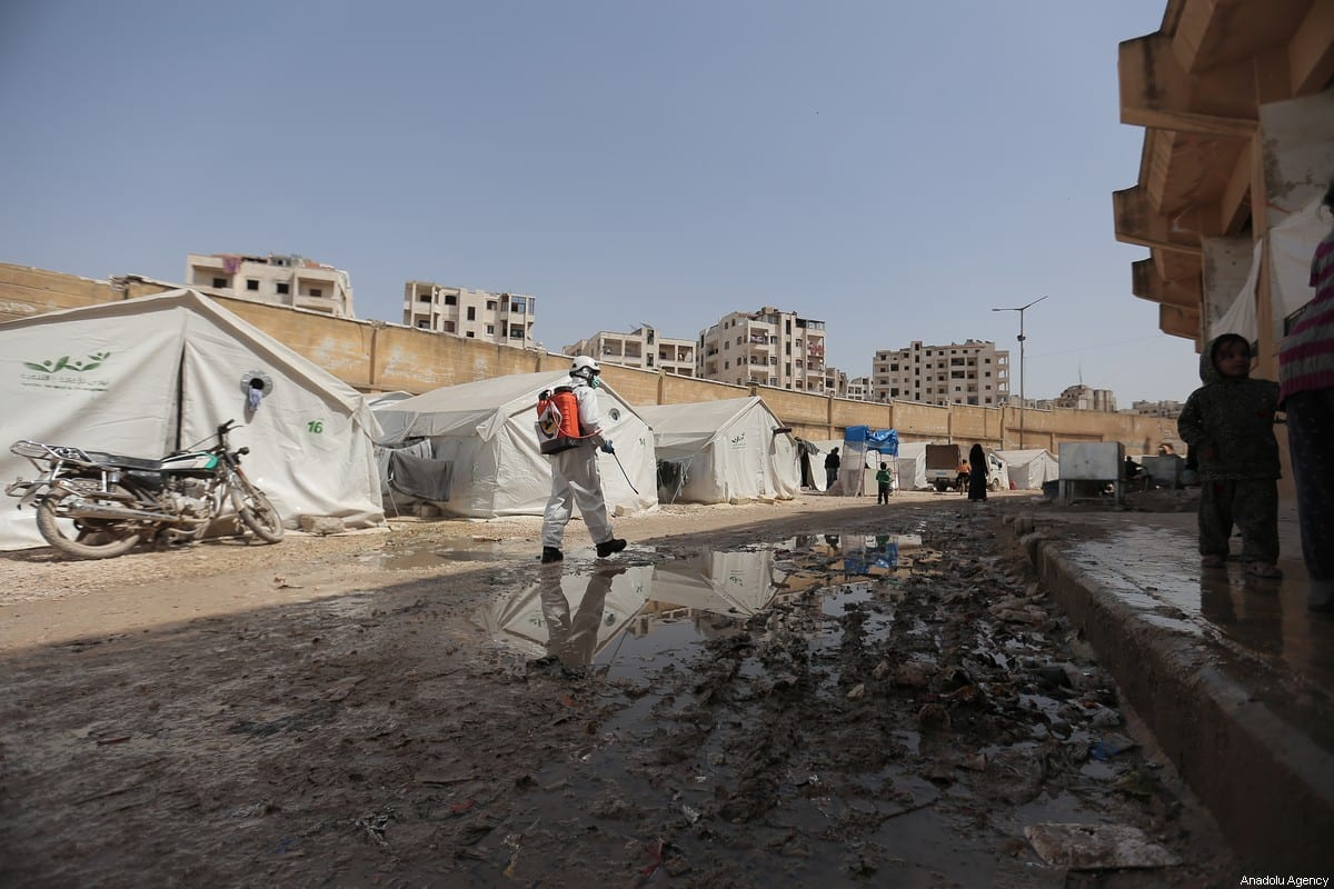 Members of the Syrian Civil Defence (White Helmets) disinfect tents inhabited by families as a preventive measure against coronavirus (Covid-19) pandemic in Idlib, Syria on March 24, 2020 [Muhammed Said - Anadolu Agency]