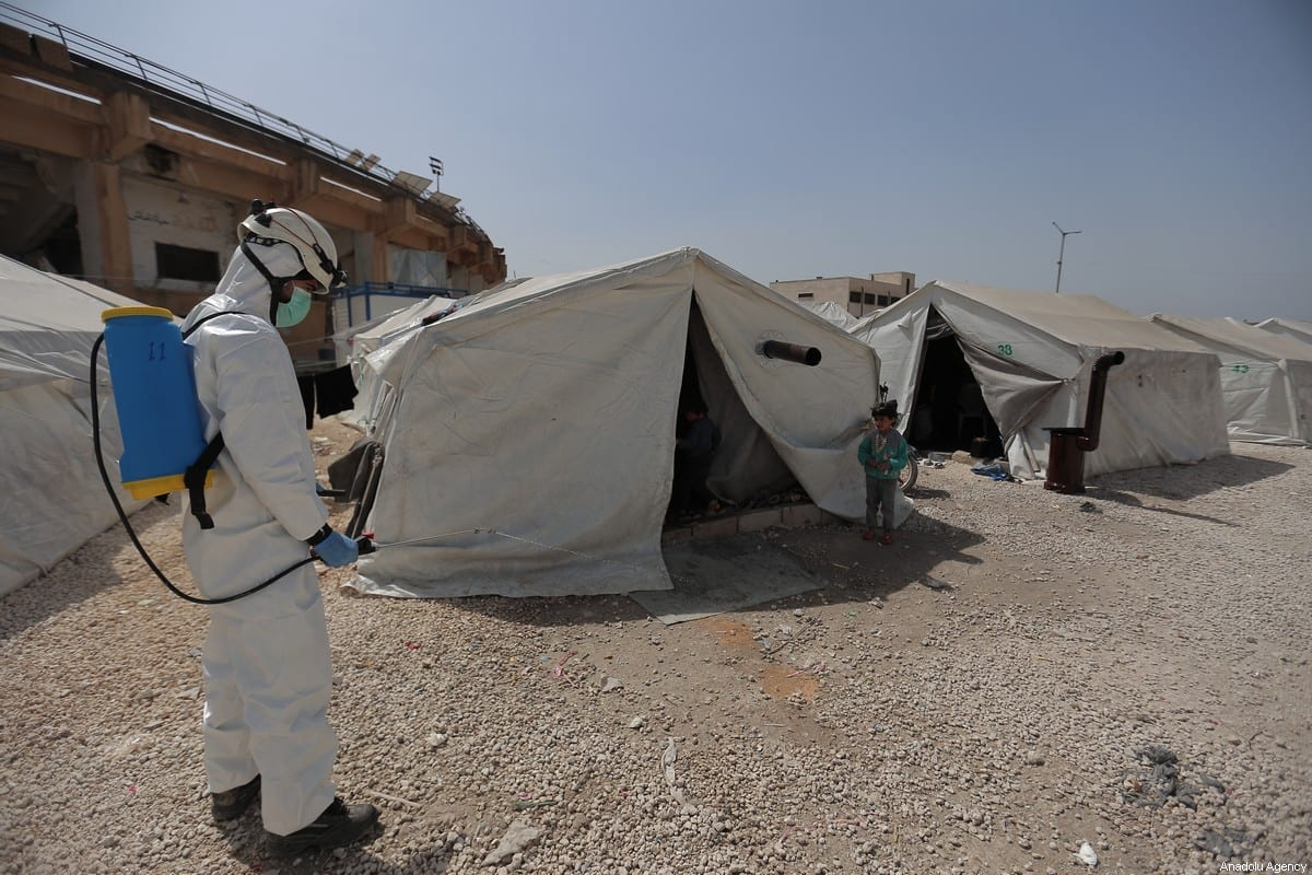 Members of the Syrian Civil Defence (White Helmets) disinfect tents inhabited by families as a preventive measure against coronavirus (Covid-19) pandemic in Idlib, Syria on March 24, 2020 [Muhammed Said / Anadolu Agency]
