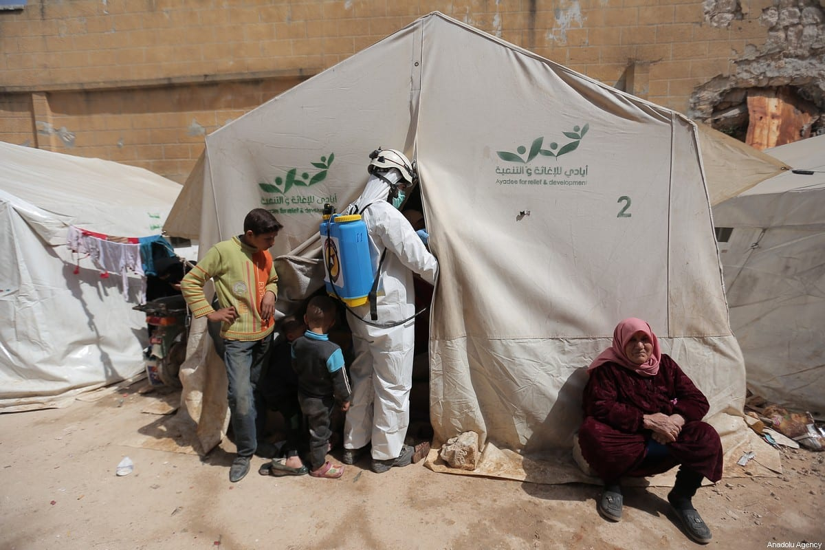 Members of the Syrian Civil Defence (White Helmets) disinfect buildings and tents where families live collectively as a preventive measure against coronavirus (Covid-19) pandemic in Idlib, Syria on March 24, 2020 [Muhammed Said - Anadolu Agency]