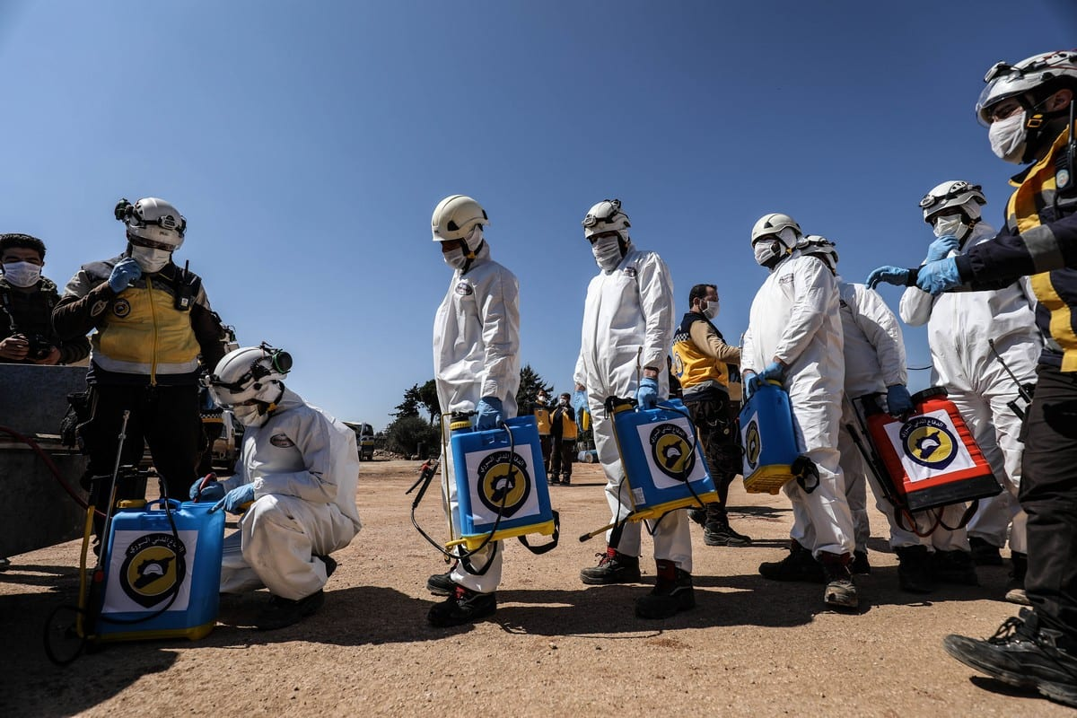 Members of the Syrian civil defense group, White Helmets, wearing protective suits, starts to carry out disinfection works around the city as part of precautions against the coronavirus (COVID-19), on 22 March 2020 in Idlib, Syria [İzzeddin İdilbi/Anadolu Agency]