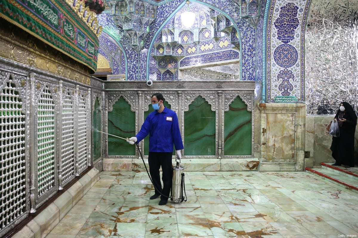An Iranian sanitary worker disinfects Qom's Masumeh shrine on February 25, 2020 to prevent the spread of the coronavirus [MEHDI MARIZAD/FARS NEWS AGENCY/AFP via Getty Images]