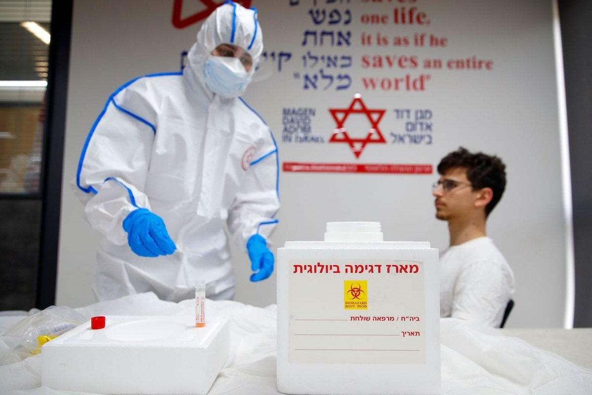 Israeli Paramedics of the Israel's National Emergency Pre-Hospital Medical Organisation at the coronavirus national operations center, perform a coronavirus test exercise on a volunteer on 26 February 2020 in the central Israeli city of Kiryat Ono [JACK GUEZ/AFP via Getty Images]