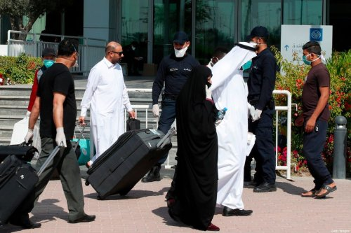 Qatari police stand outside a hotel in Doha as a medical worker walks alongside people wearing protective masks over fears of coronavirus, on 12 March 2020 [AFP/Getty Images]