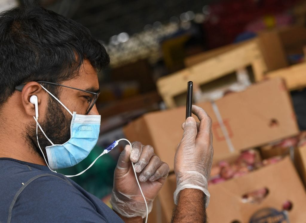 A worker speaks on the phone while wearing a face mask and gloves at a market in Dubai on 21 March, 2020 amid coronavirus outbreak [KARIM SAHIB/AFP via Getty Images]