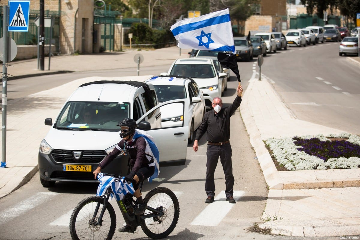 A demonstator wearing a protective mask holds the Israeli flag and a black flag as he protests outside the Israeli Parliament on 23 March 2020 in Jerusalem, Israel. Thousands of israelis gathered to protest against Israeli Prime Minister Benjamin Netanyahu, saying he is making anti-democratic steps during the Coronavirus outbreak. [Amir Levy/Getty Images]