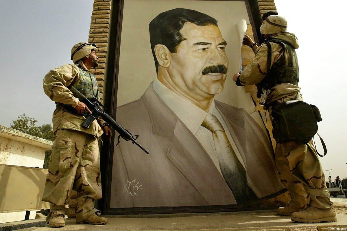 U.S. Marine Major Bull Gurfein (R) pulls down a poster of Iraqi President Saddam Hussein March 21, 2003 in Safwan, Iraq. [ Chris Hondros/Getty Images]