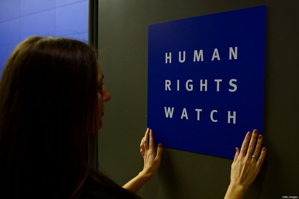 A woman puts a logo of US-based rights group Human Rights Watch on the door as she prepares the room before their press conference to release their annual World report on January 21, 2014 in Berlin [JOHN MACDOUGALL/AFP via Getty Images]