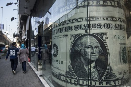 People walk past a currency exchange shop displaying a giant US dollars banknote in downtown Cairo on November 3, 2016. [KHALED DESOUKI/AFP via Getty Images]