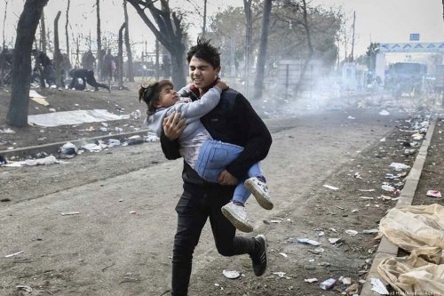 A man, whilst carrying his daughter, run for cover after Greek forces fire at refugees at the Greece border, 11 March 2020