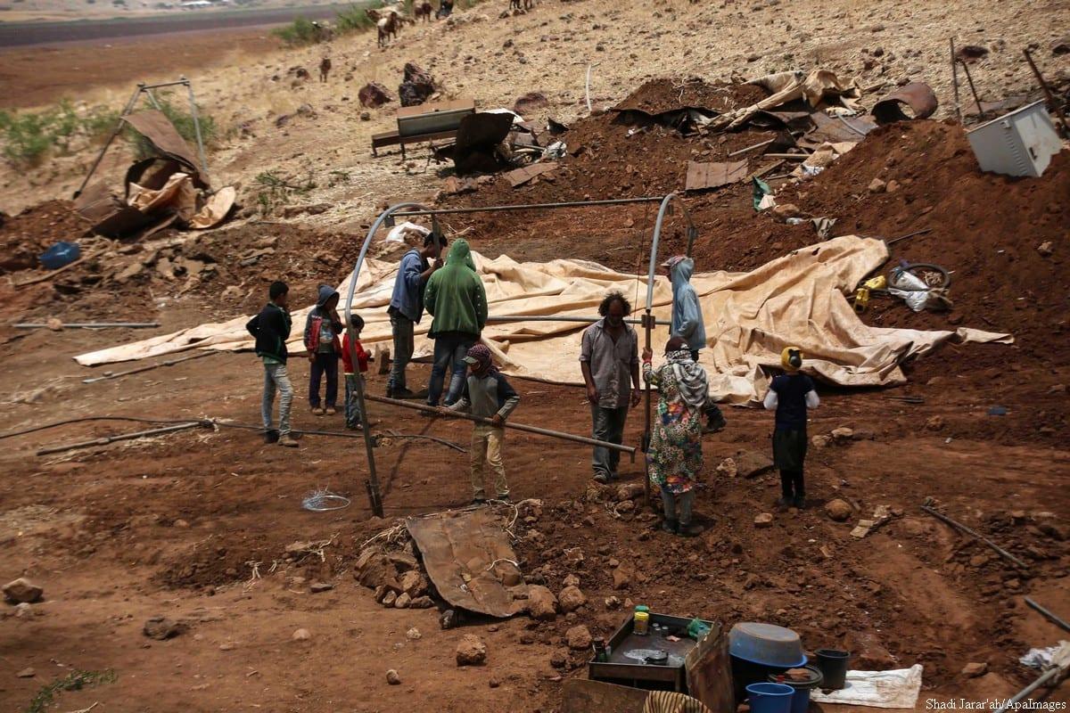 Bedouin Palestinians inspect their belongings after the Israeli troops demolished their tents in the Jordan valley, 12 June 2019 [Shadi Jarar'ah/ApaImage]