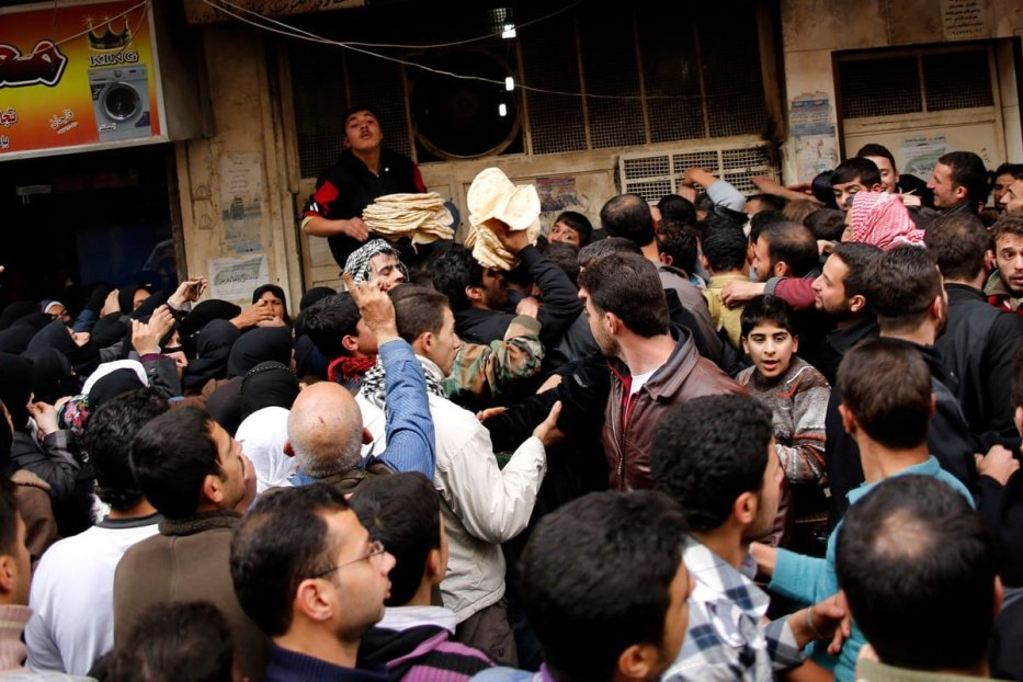 Residents gather around to buy bread in Syria's Aleppo province, on 16 December 2012 [PRASHANT RAO/AFP/Getty Images]