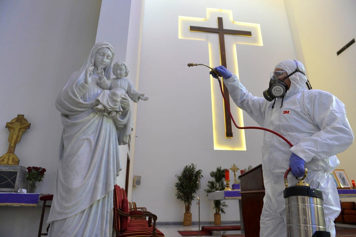 A health official wearing protective suit sprays disinfectant at a church as a precaution against the coronavirus (Covid-19) in Beirut, Lebanon on 5 March 2020 [Hussam Chbaro/Anadolu Agency]