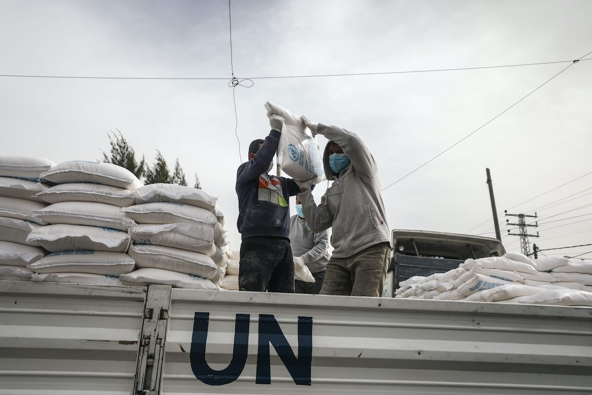 Members of the United Nations Relief and Works Agency (UNRWA) prepare food aids for refugees due to coronavirus (Covid-19) pandemic in Deir Al Balah, Gaza on 31 March 2020. UNRWA launched a new mechanism in the Gaza Strip to ensure that food aid is delivered to refugees' houses. [Ali Jadallah - Anadolu Agency]