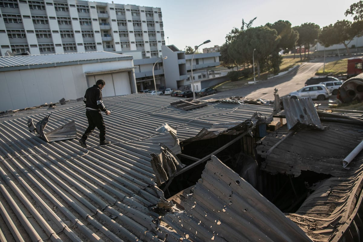 A man inspects the roof of the hospital after Haftar forces' rocket attacks hit the al-Hadra Hospital, which has many patients with chronic illnesses and especially coronavirus (COVID-19) , in Tripoli, Libya on 5 April 2020. [Amru Salahuddien - Anadolu Agency]